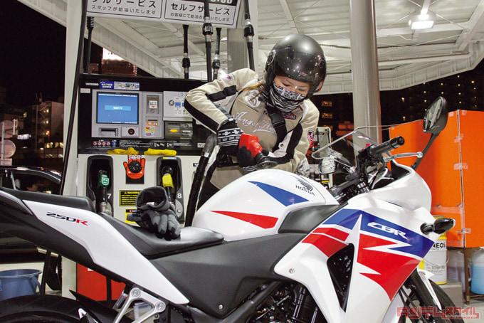 ガソリンスタンドでバイクに給油中の様子
