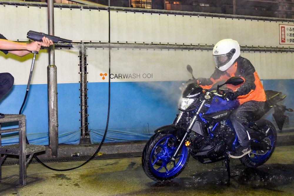 ワイズギア YAR19 サイバーテックス2 ダブルガードレインスーツに洗車場の洗車ガンで水をかけている様子