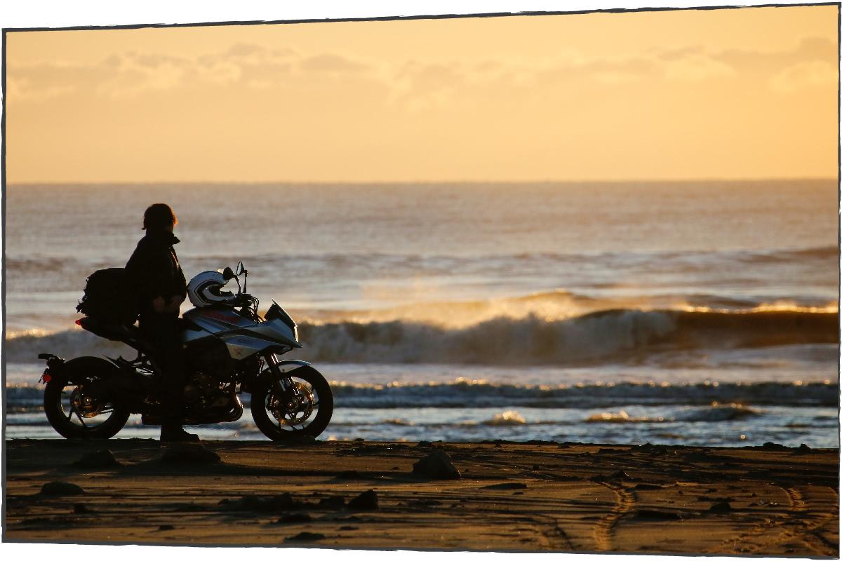 朝焼けの海岸にバックに佇むKATAMA