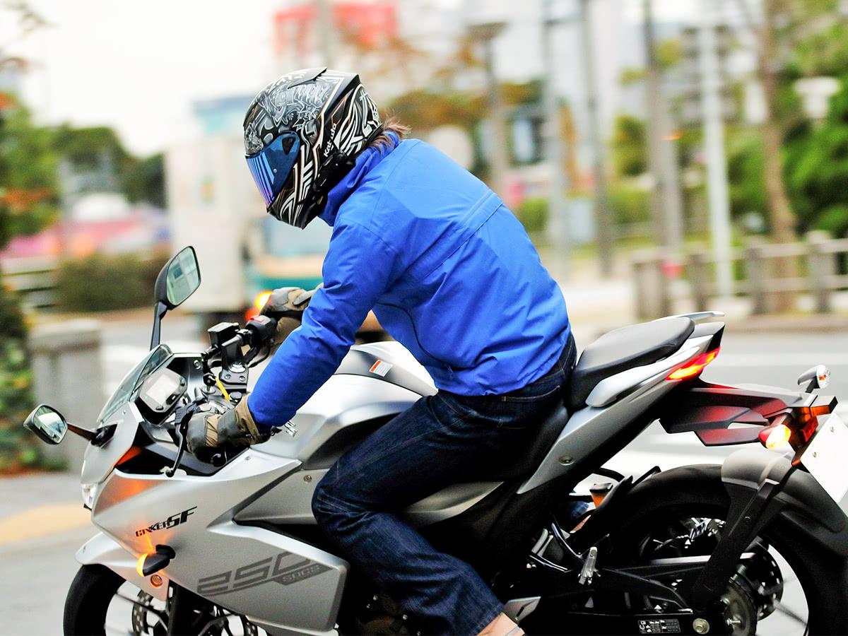 GOLDWIN GSM22900 MOTORCYCLE GWM ゴアテックスマルチフーデッドジャケットを着てバイクで走るライダー