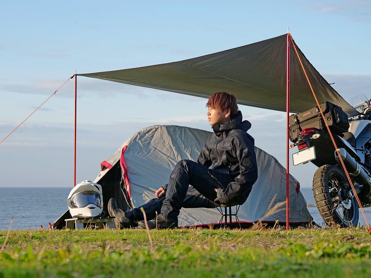 GOLDWIN MOTORCYCLE GWM ゴアテックスデニムジャケットとゴアテックスデニムパンツを着てキャンプをするライダー