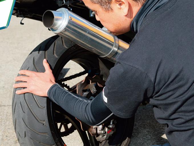バイクのタイヤ表面を触って温度を確かめている様子